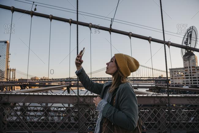 USA- New York- New York City- female tourist using smartphone on Brooklyn Bridge in the morning light