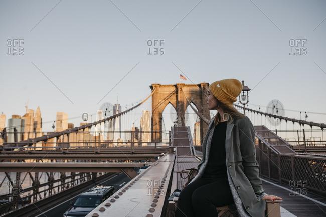 USA- New York- New York City- female tourist sitting on Brooklyn Bridge in the morning light