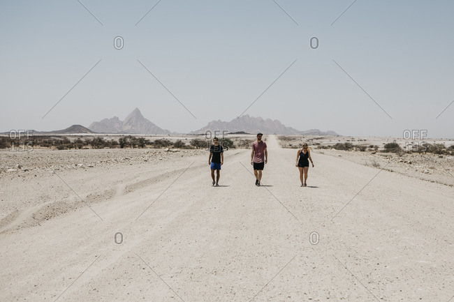 Namibia- friends walking on the road to Spitzkoppe