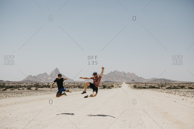 Namibia- two friends jumping on the road to Spitzkoppe