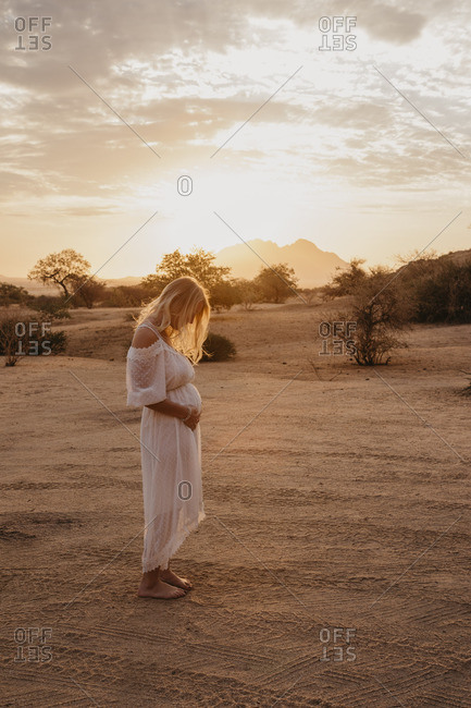 Namibia- Spitzkoppe- woman in white dress in desert landscape at sunset