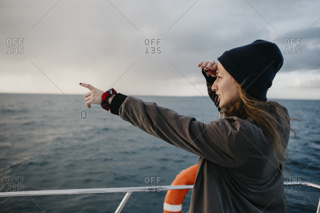 South Africa- young woman with woolly hat during boat trip- pointing finger