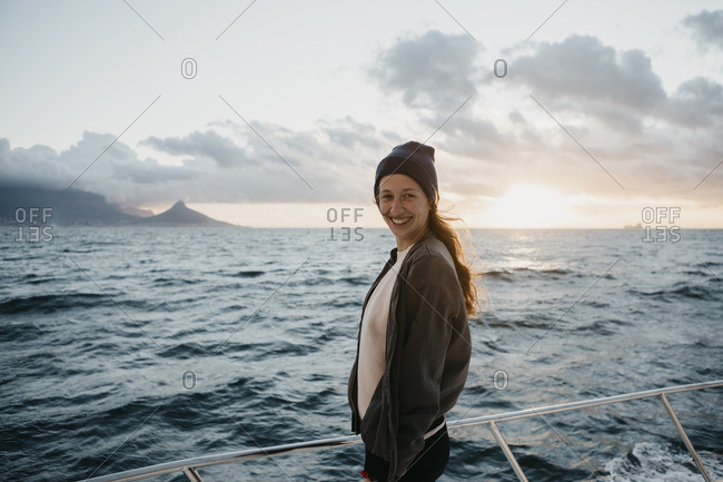 South Africa- young woman with woolly hat smiling during boat trip at sunset