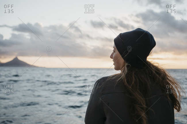 South Africa- young woman with woolly hat during boat trip at sunset