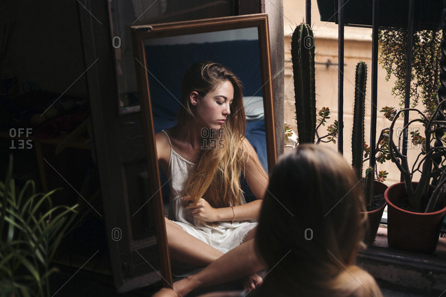 Mirror image of young woman sitting on the floor at home relaxing