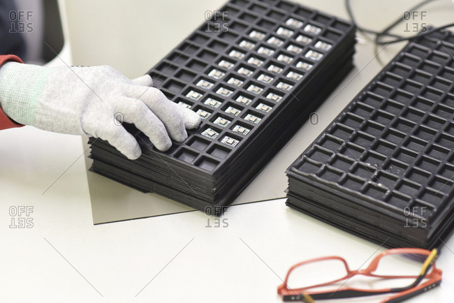 Close-up of woman loading circuit boards in a factory