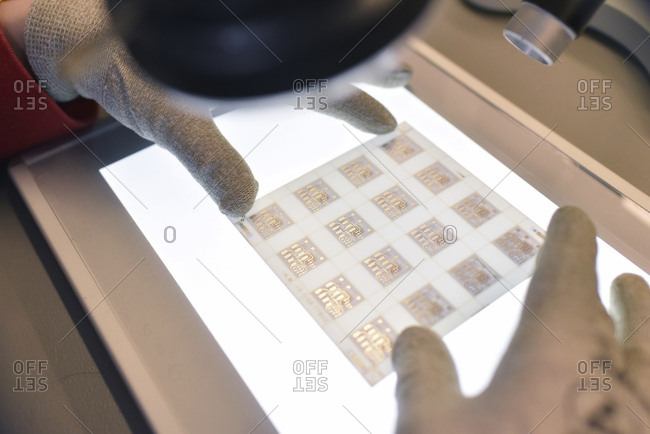 Close-up of woman working on the quality control in the manufacturing of ceramic circuit boards for the electronics industry