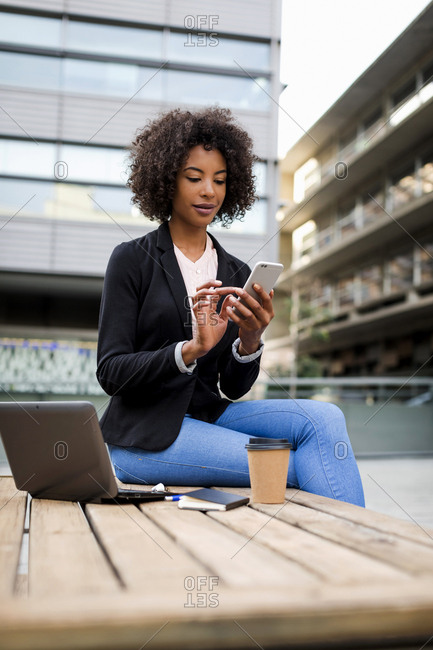 Portrait of businesswoman sitting on table outdoors using smartphone
