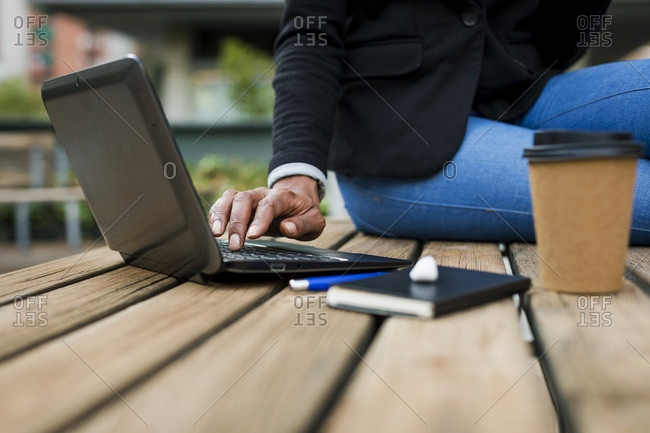 Businesswoman sitting on table outdoors using laptop- partial view