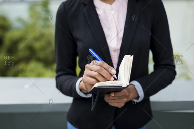 Hand of businesswoman taking notes outdoors- close-up