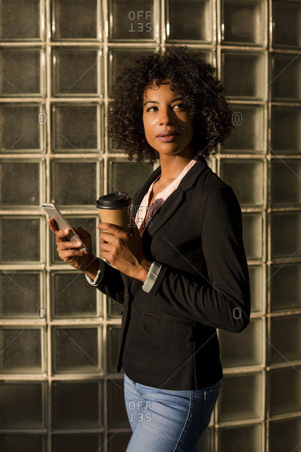 Portrait of businesswoman with coffee to go and cell phone at evening twilight
