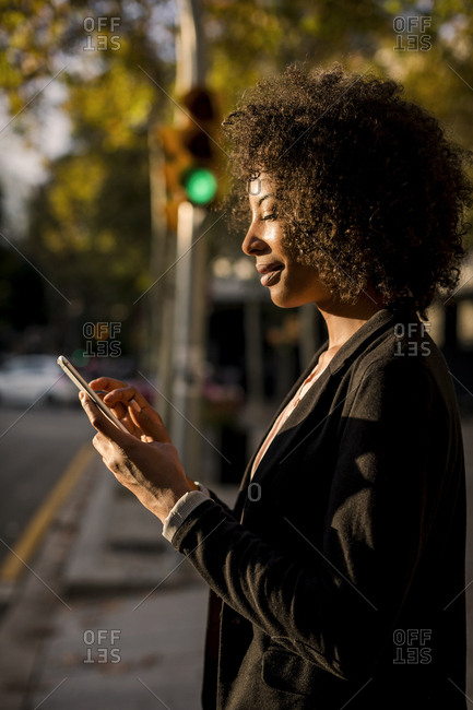 Smiling businesswoman using cell phone on the street at evening twilight