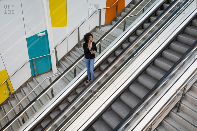 Businesswoman on the phone standing on escalator