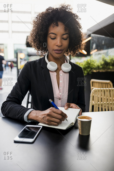 Portrait of businesswoman taking notes at pavement cafe