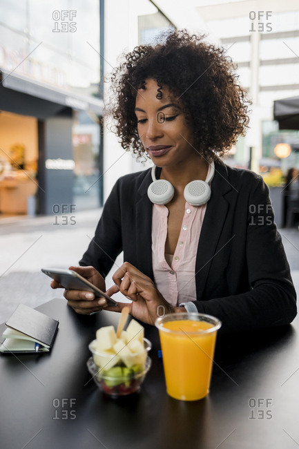 Portrait of businesswoman using cell phone at pavement cafe