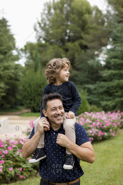 Happy father carrying son on shoulders in park