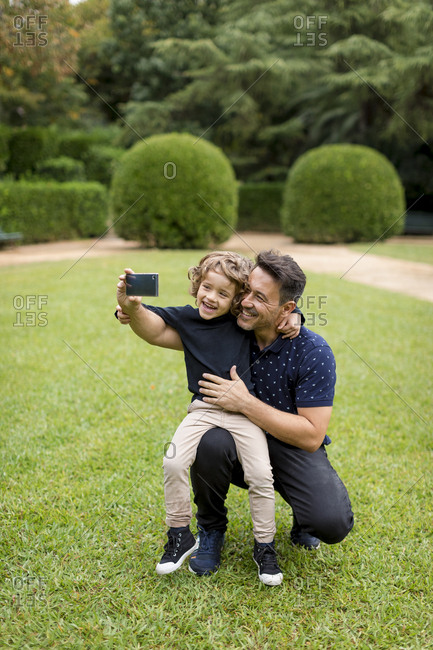 Happy father and son on taking a selfie in park