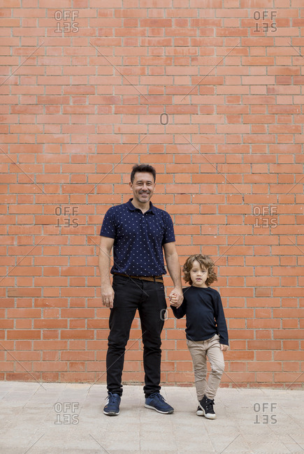 Portrait of father and son standing hand in hand at brick wall