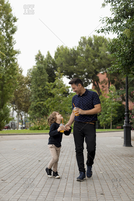 Happy father and son walking hand in hand with soft drinks