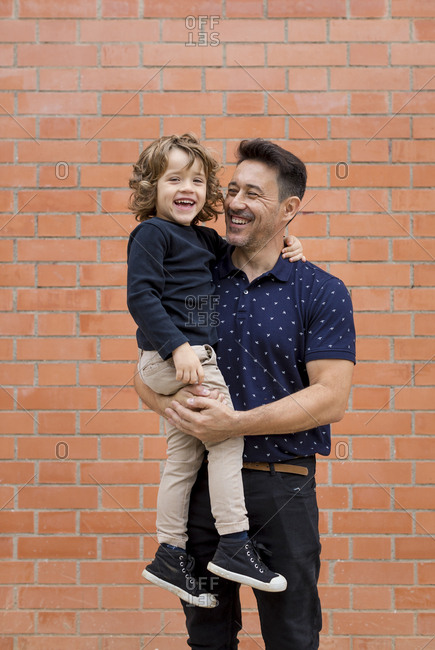 Happy father carrying son at brick wall
