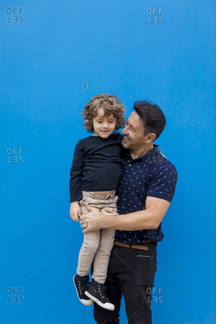 Happy father carrying son at blue wall