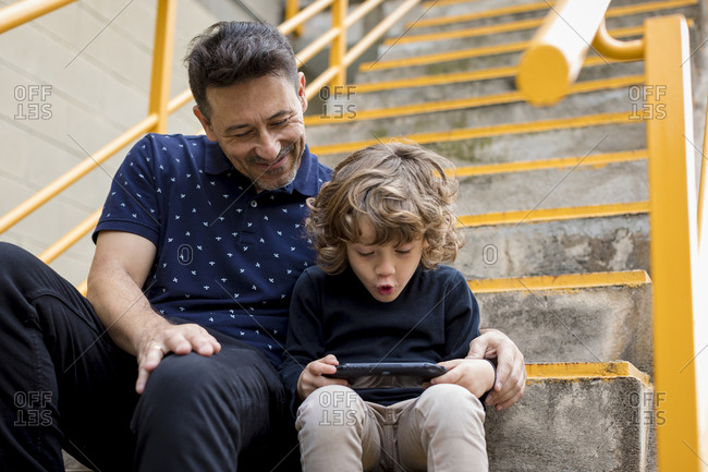 Father watching son playing with handheld game console