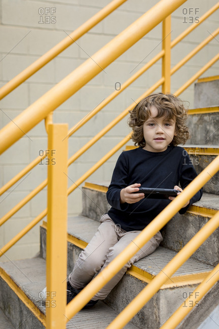 Portrait of boy sitting on stairs with handheld game console