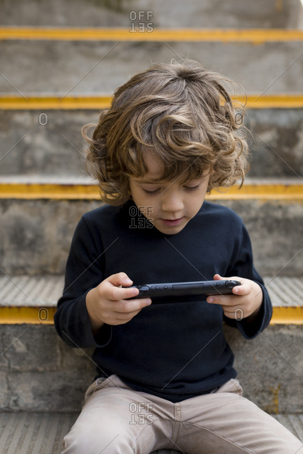 Boy sitting on stairs playing with handheld game console