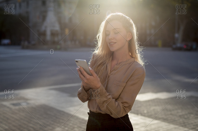 Smiling young businesswoman using cell phone in the city