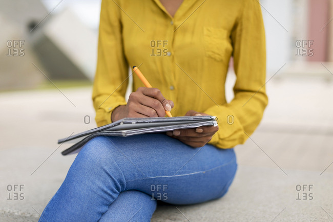 Woman sitting on bench taking notes- partial view
