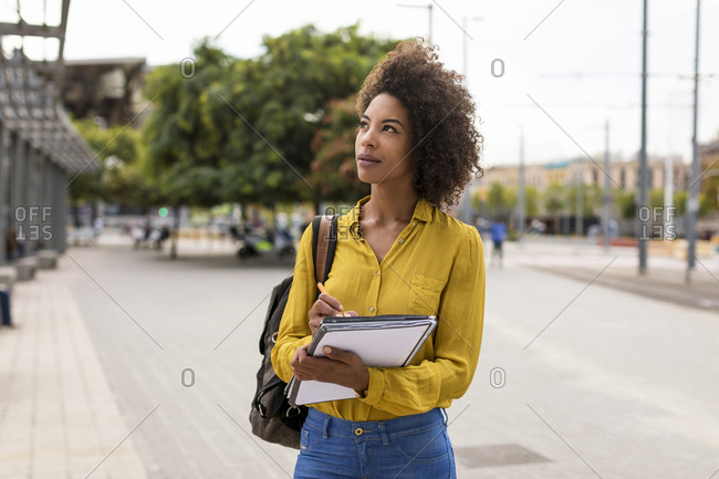 Portrait of woman with backpack- documents and pencil looking up