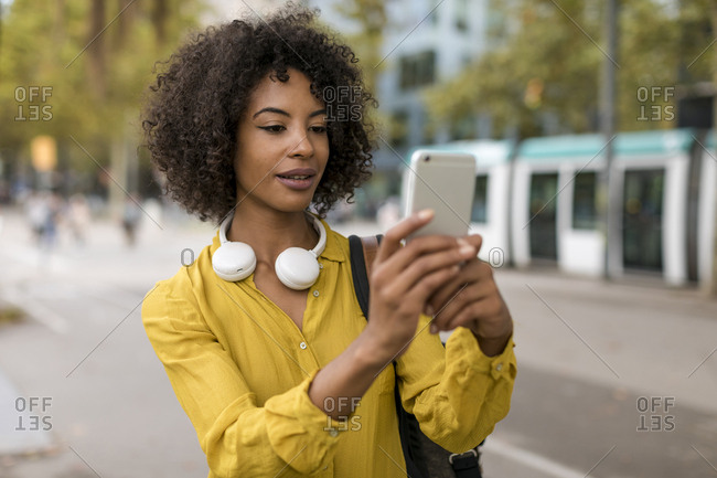 Portrait of woman with headphones taking selfie with smartphone