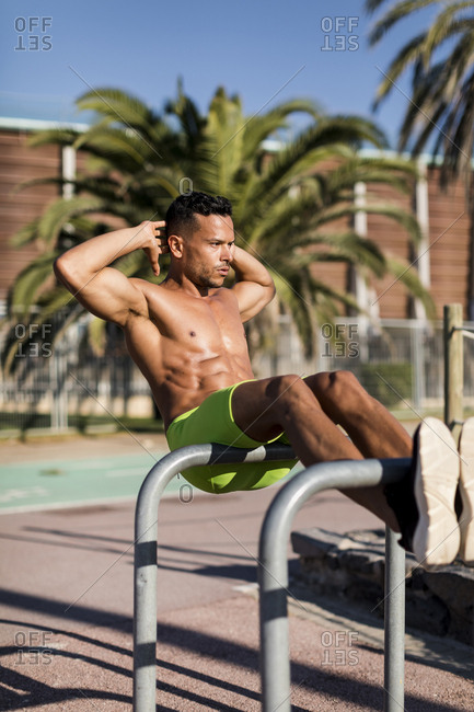 Bare-chested muscular man doing sit-ups outdoors