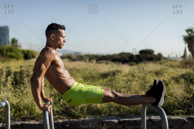 Bare-chested muscular man exercising outdoors