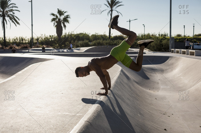 Bare-chested muscular man exercising in a skate park