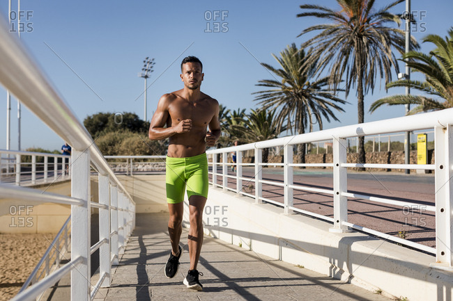 Bare-chested man running on promenade