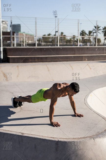Bare-chested muscular man doing push-ups in a skate park