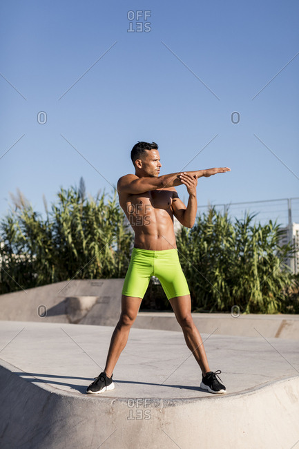 Bare-chested muscular man doing stretching exercise in a skate park
