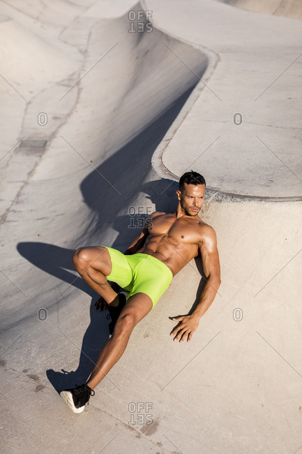 Bare-chested muscular man posing in a skate park