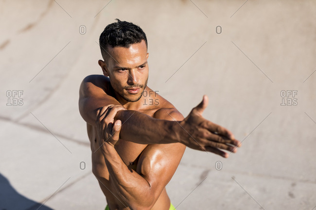 Bare-chested muscular man doing stretching exercise outdoors