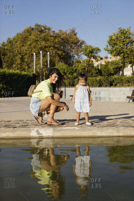 Happy mother with daughter looking at their mirror image in a pool in a park