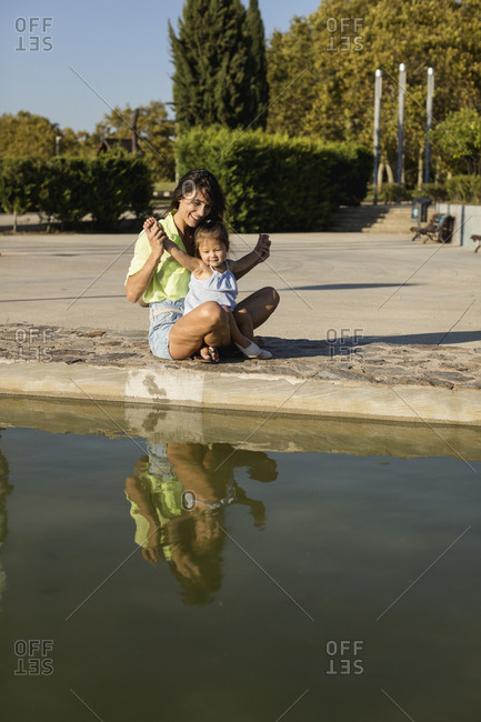 Happy mother with daughter at a pool in a park
