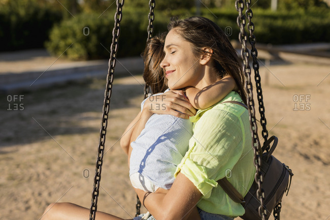 Smiling mother hugging daughter on a playground