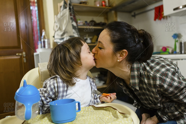 Mother kissing toddler son in high chair in kitchen