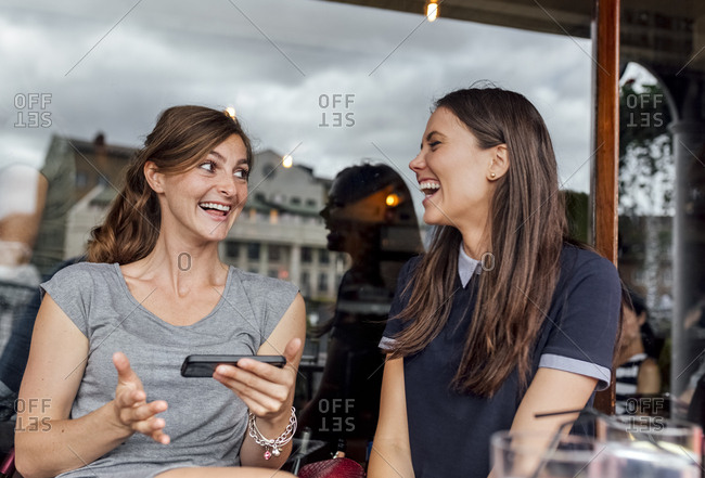 Two women having fun with their smartphone on a terrace