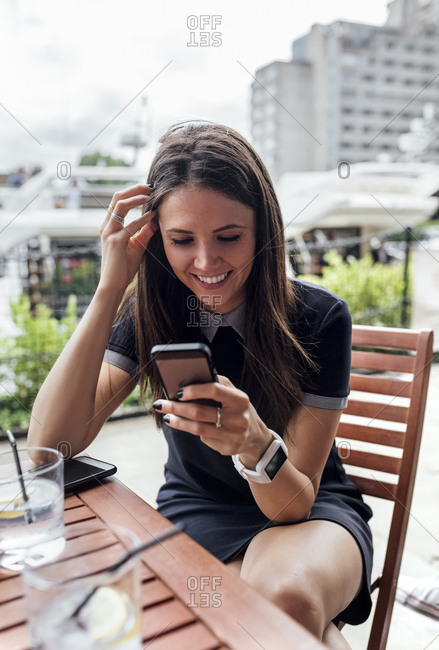 Young beautiful woman using her smartphone on a terrace