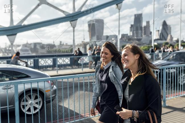 UK- London- two happy women walking on the Tower Bridge