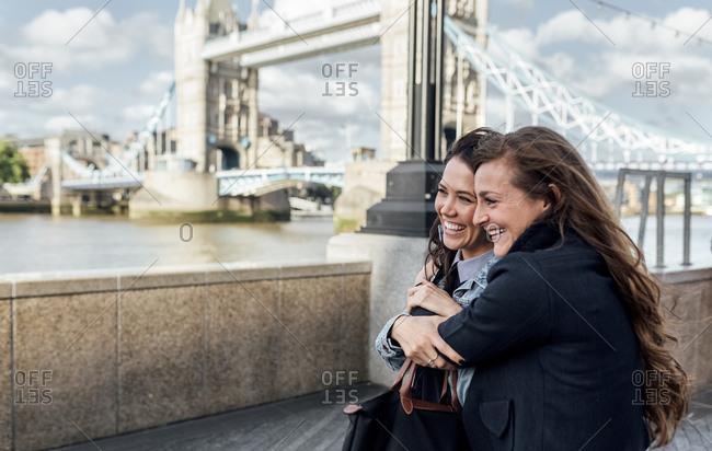 UK- London- two happy women near the Tower Bridge
