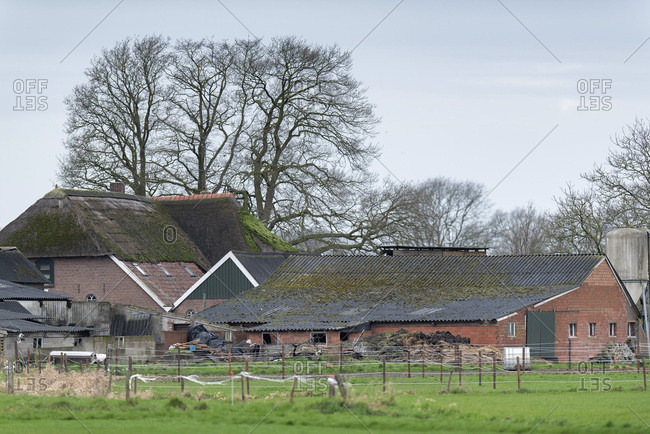 A brick farmhouse and farm building in the countryside