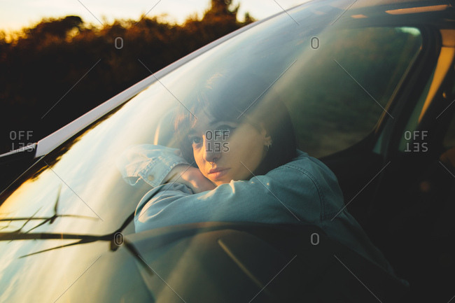 Young woman in a car, looking through the window into distance